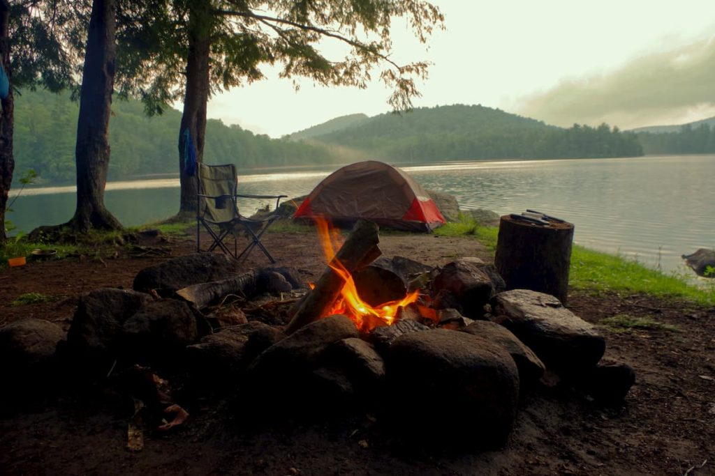 Primitive campsite at the lakeshore, firepit and a travel seat to relax in by the fire.