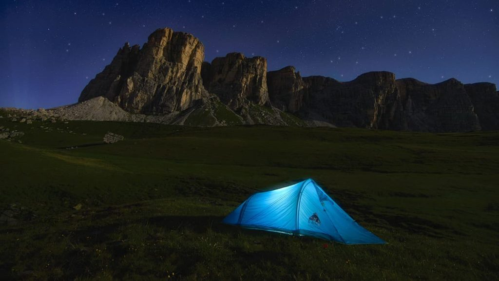 What is a Backpacking Tent Footprint with tent on the grass by a awesome rock formation at night.