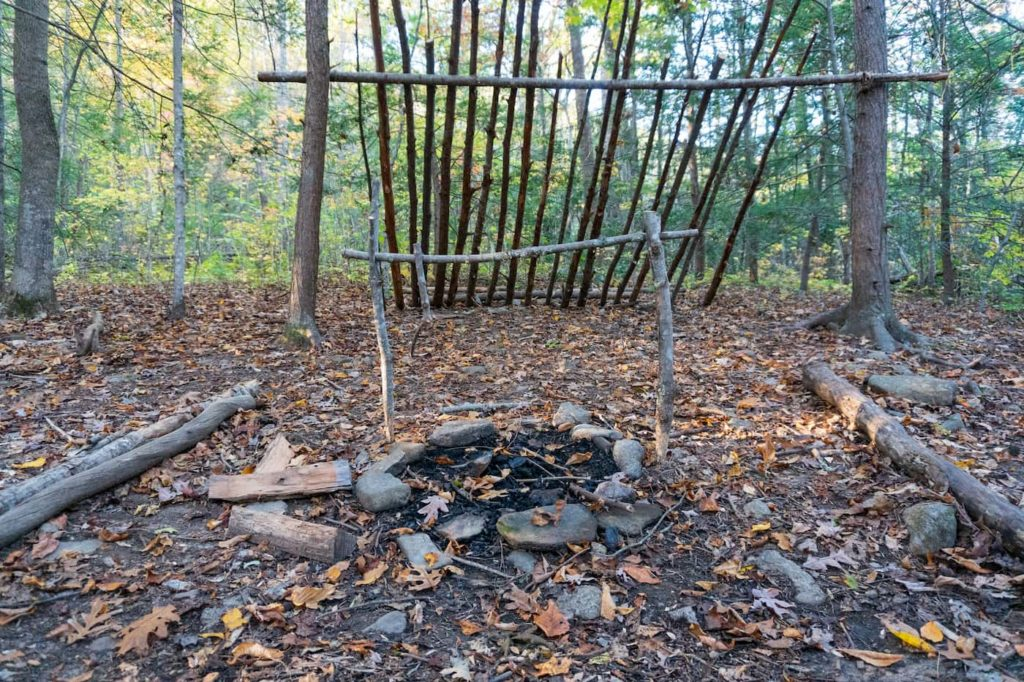 Primitive camping site with a stone circle for fire and branches for seats. What Does Primitive Camping Mean? It is to enjoy outside without the hustle and bustle of a campground.