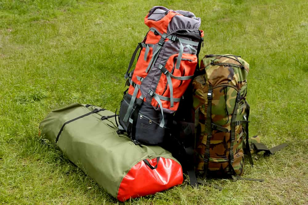 Backpacks sitting on the grass ready for the hike to start again - What Are the Backpacking Big Four