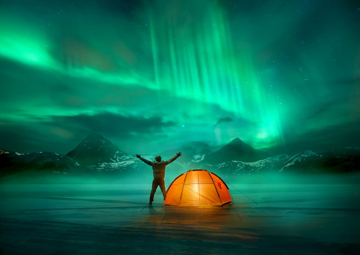 A man camping in wild northern mountains with an illuminated tent viewing a spectacular green northern lights aurora display.