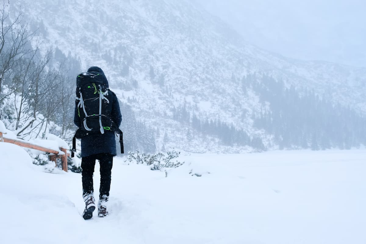 A man hiking on a cold snowy hill, with boots and gloves and full thru hiking backpack setup