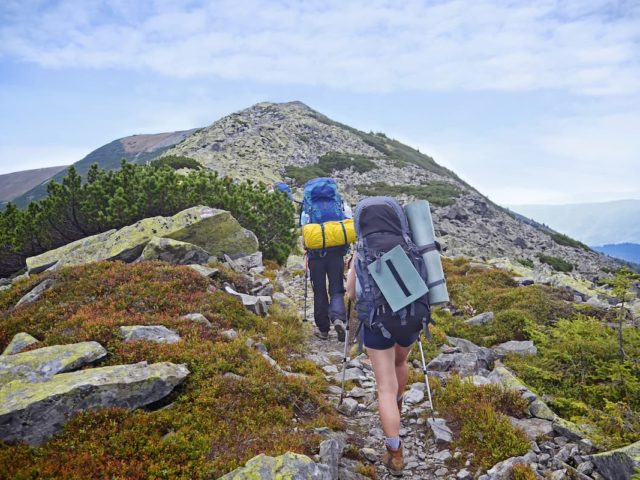 Young people hiking up a mountain with 30+ pound backpacks on.