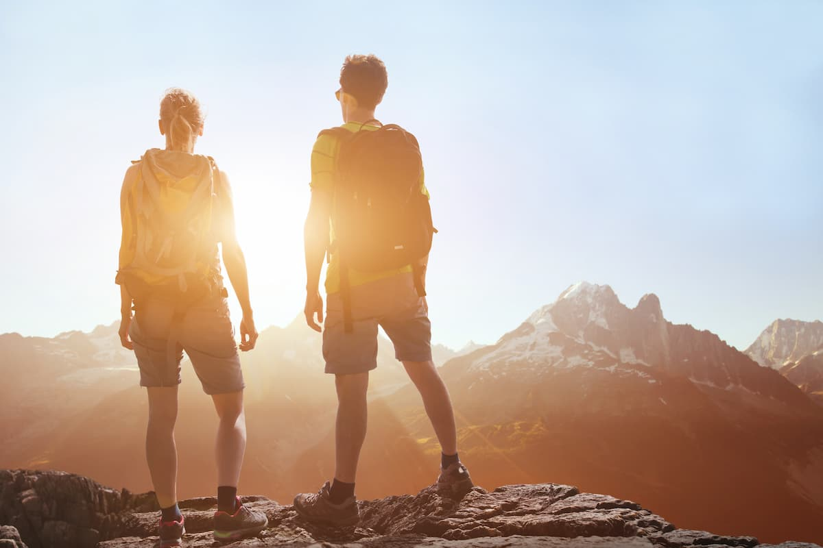 People traveling, hiking in mountains, couple of hikers looking at panoramic landscape view, summer trekking