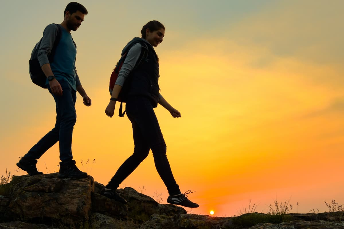 Couple of Young Happy Travelers Hiking with Backpacks on the Beautiful Rocky Trail at Warm Summer Sunset