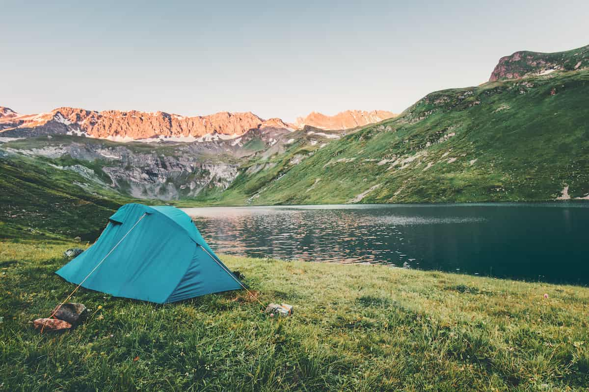 blue tent on the grass located by a lake and surrounded by amazing mountains.